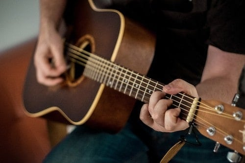 Person playing an acoustic guitar